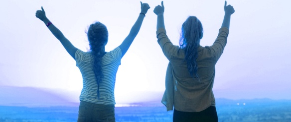 Two women standing with arms and thumbs up